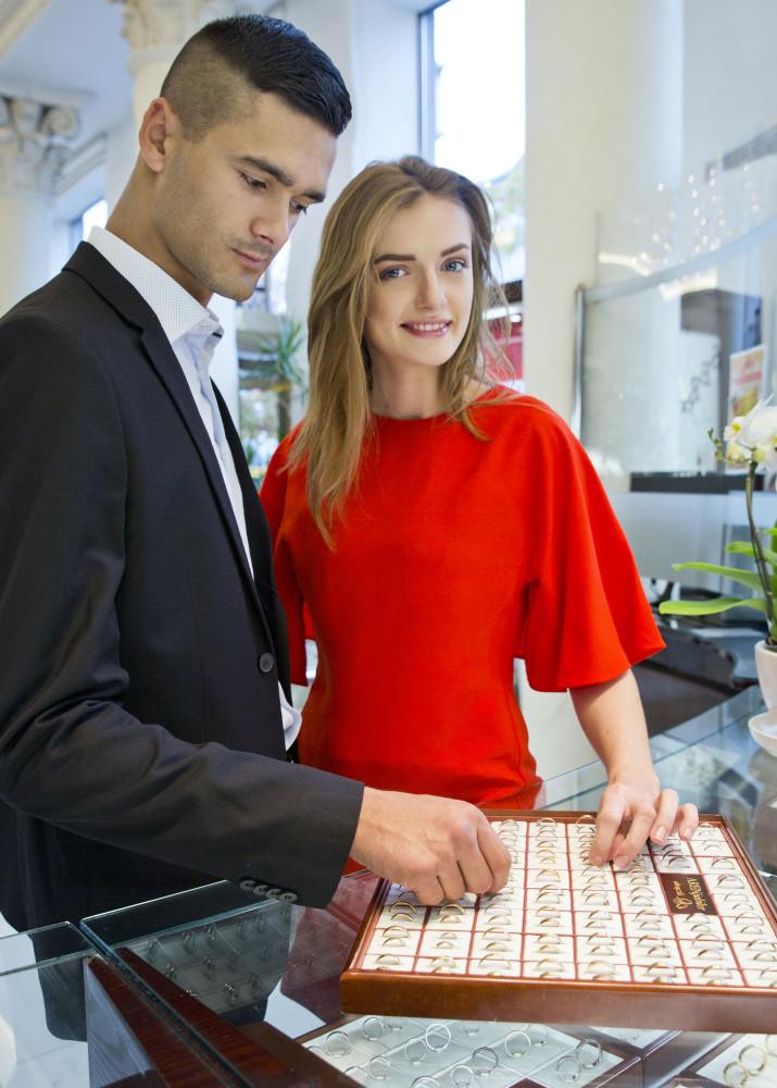 dziewczyna z chłopakiem ogląda złote pierścionki